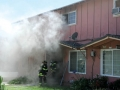 The two story apartment building billows smoke out the front door during a fire Wednesday aftenoon on Nash Rd.